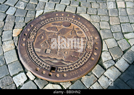 Decorated Drainage grate in the compel stone pavement of the Bryggen in Bergen, Norway - Stock Image