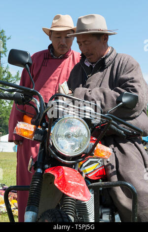 Naadam Festival in Khatgal, Mongolia.Two men counting money on a motorcycle. - Stock Image