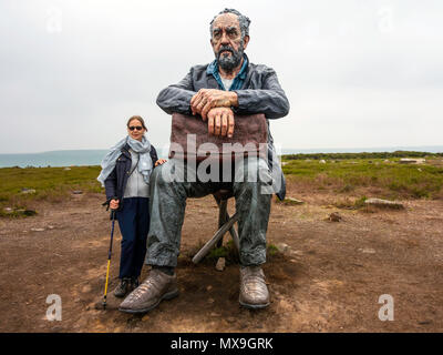 A senior lady standing by the Seated Man Sculpture by artist Sean Henry on Castleton in the North Yorkshire Moors National Park overlooking Westerdale - Stock Image