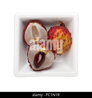 Lychees in a square bowl isolated on white background - Stock Image