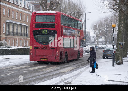 A woman waits to cross the street in Muswell Hill as the 'Beast from the East' severe cold weather and snow - Stock Image