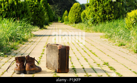 It's time to wander the earth! Shabby ankle boots and a vintage suitcase in the middle of a yellow brick road. Sixteen-by-Nine crop. - Stock Image