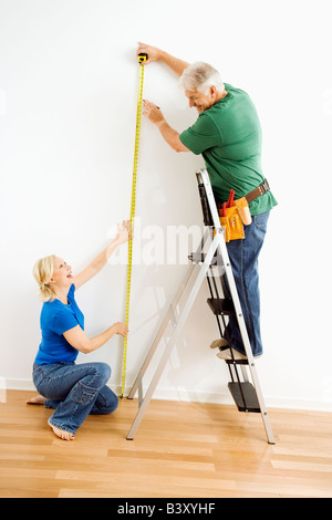 Middle aged couple measuring wall with tape - Stock Image