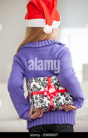 Girl In Santa Hat Hiding Christmas Gift Behind Back - Stock Image
