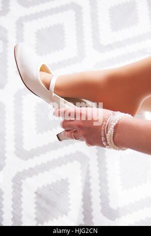 Bride,Shoe,Brauhuh,Pumps,White,Dress,Stretches,Hand,Finger,Stretched,Model,Arm,Woman,Brautschuhe,beautiful,intimate,alone,weddin - Stock Image