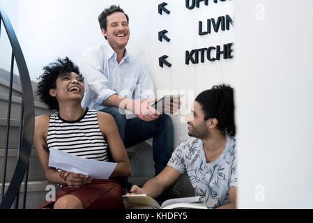 People sitting together in stairwell laughing - Stock Image