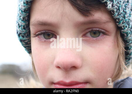 Closeup of a frustrated green eyed little girl that is close to tears - Stock Image