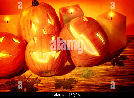 Closeup photo of a carved pumpkins with scary faces and glowing candles on the table, festive party decoration for - Stock Image
