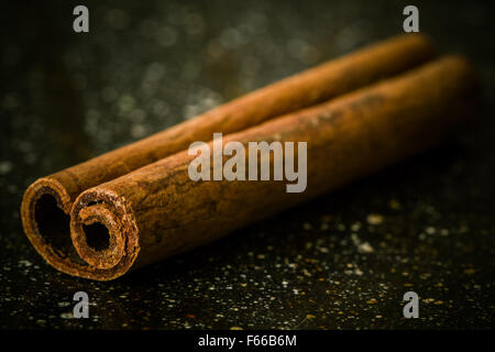 cinnamon on a black marble desk from close - Stock Image