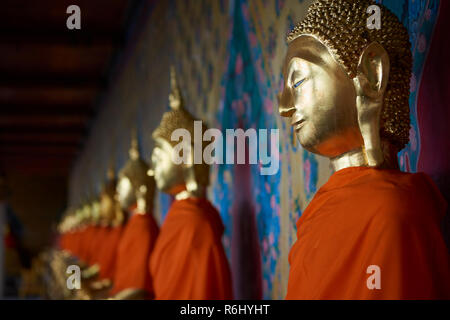 Several golden Buddha statues lined up in a diminishing perspective under the cover of one of the Ordination Hall in Bangkok, Thailand. - Stock Image
