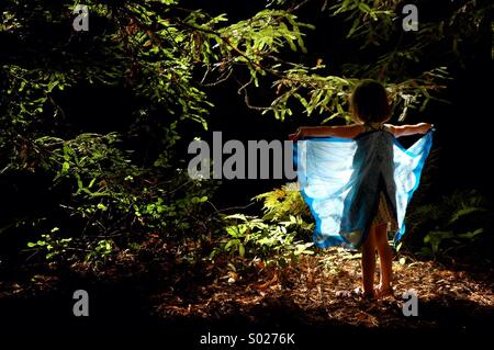 A little girl spreads fairy wings in forest. - Stock Image