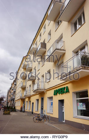 Poznan, Poland - March 8, 2019: Pharmacy shop in a apartment building with balconies. Bicycle parked by the entrance on a sidewalk. Located in the Slo - Stock Image