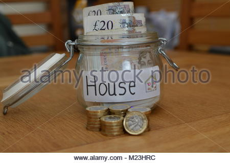 Class jar with house written on white label with currency notes inside and new one pound coins stacked in front. - Stock Image