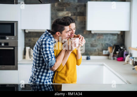 A young couple standing in a kitchen at home, drinking coffee. - Stock Image