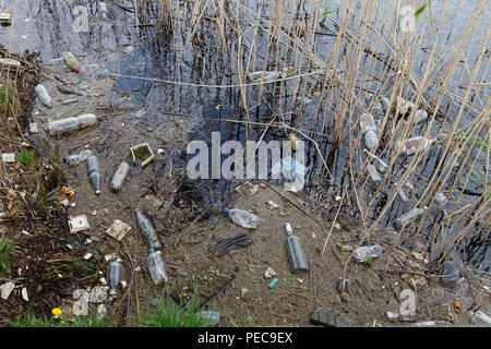 Leftover garbage and glass bottles on the banks of the Peene, garbage in nature, Nature Park Peental - Stock Image
