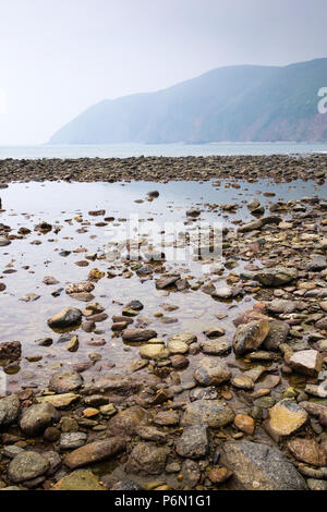 The rocky beach at Lynmouth, North Devon, with reflection and view north-east towards Foreland Point. - Stock Image