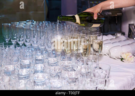 The waiter pours champagne into glasses from a bottle in a restaurant. Catering, banquet - Stock Image