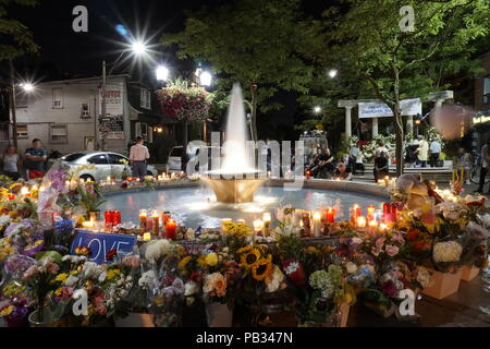 Candel light vigil with flowers and messages in Alexander The Great Parkette on Greek Town Danforth Avenue and Logan Street after deadly mass shooting on July 22, 2018 - Stock Image