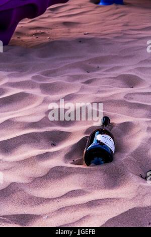 Bottle of Prosecco - italian wine lying on the sand. - Stock Image
