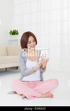 Young woman holding touch pad and looking down with smile, - Stock Image
