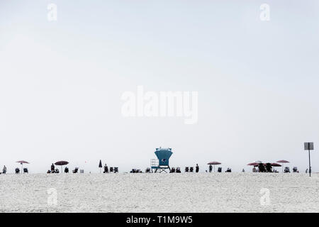 Lifeguard tower and people relaxing under umbrellas on sunny beach, San Diego, California, USA - Stock Image
