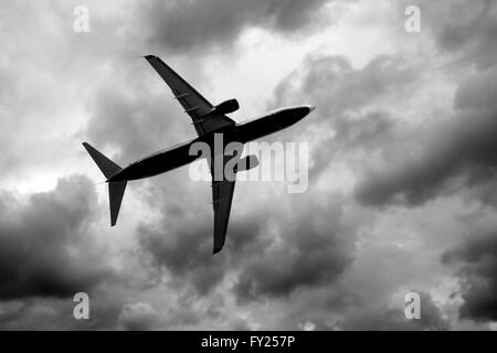Silhouette of jet in dark cloudy sky - Stock Image