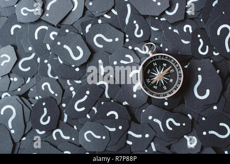 Metal compass on question mark background. Concept of travel, navigation, explore and where to go - Stock Image