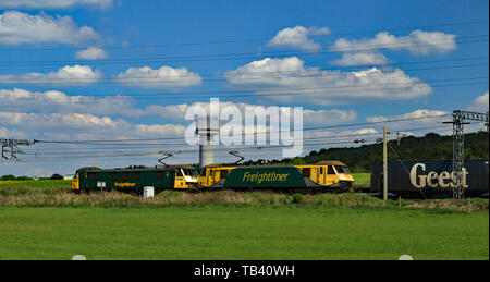 Freightliner electric locomotives 90016 and 90049 pass the research laboratory water tower at Daresbury with a intermodal freight train to Scotland. - Stock Image
