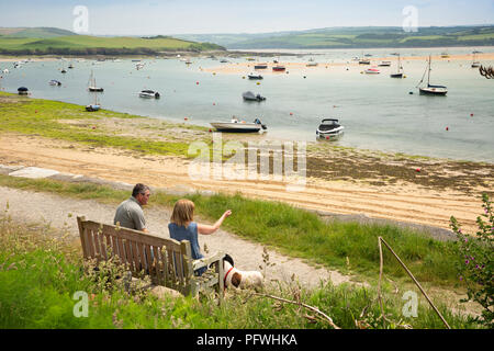 UK, Cornwall, Rock, couple sat on waterfront bench beside River Camel - Stock Image