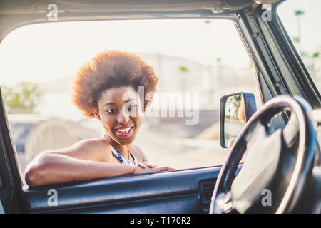 Young beautiful alternative black african girl with afro hair style smile and look inside a car in travel or outdoor leisure activity - diverse look f - Stock Image