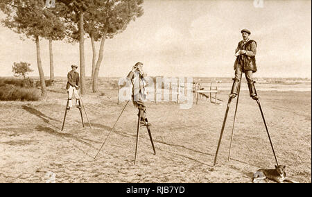 Men on stilts in the marshy Les Landes, south west France. When resting they slant the stilts as if sitting down, and prop themselves up with a third pole. - Stock Image