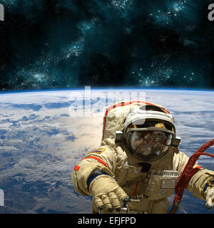 A cosmonaut floats in space above Earth. Stars shine in the background. - Stock Image