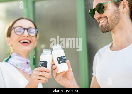 Young vegetarian couple drinking oat and almond milk in bottles standing together on the green background - Stock Image