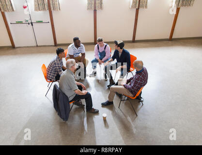 Men talking in group therapy circle - Stock Image