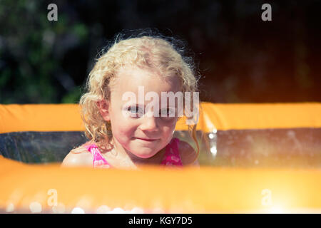 girl in paddling pool - Stock Image