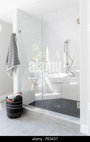 A high end residential bathroom shower stall with white tiles and towel - Stock Image