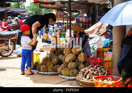 DA LAT, VIETNAM - SEPTEMBER 23: A Vietnamese woman with a child buys durian on the street market on September 23, 2018 in Da Lat, Vietnam. - Stock Image