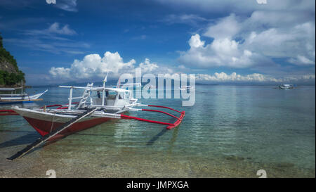 Traditional Filipino wooden outrigger banca boat on tropical island with calm, clear sea. Puerto Galera, Mindoro, Philippines. - Stock Image