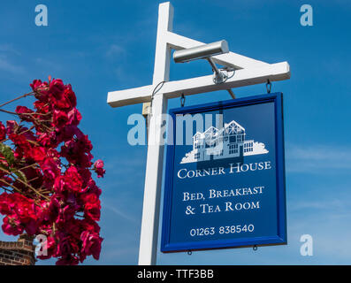 Blue sign with white woodwork, next to a pink rose bush, with blue sky: 'Corner House, Bed, Breakfast & Tea Room'. West Runton, Norfolk, England, UK. - Stock Image