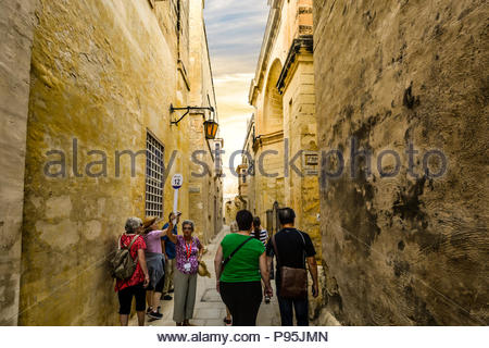 A tour guide waits for her tour group to catch up during a walking tour of the medieval walled city of Mdina, Malta - Stock Image