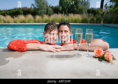 Fully clothed gay couple drinking champagne in swimming pool - Stock Image