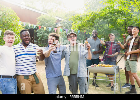 Happy, exuberant male friends drinking beer and singing during backyard barbecue - Stock Image
