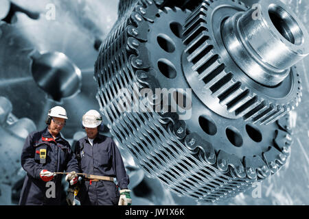 two industry workers with giant cogs machinery in background - Stock Image