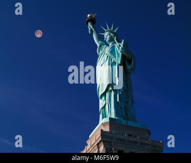 Statue of Liberty and full moon at dusk ,Liberty Island, New York, USA - Stock Image