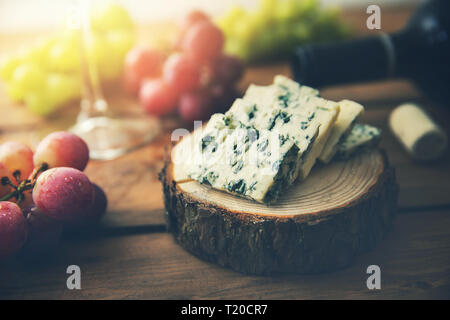 dor blue cheese on wood log slice with grapes and wine bottle - Stock Image