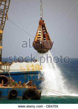 Greek building a sea wall harbour water pouring from crane Greece - Stock Image