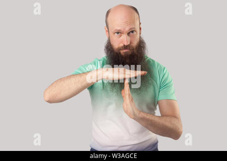 Timeout, I need more time. Portrait of worry middle aged bald bearded man in light green t-shirt standing and showing T gesture, looking and asking . - Stock Image