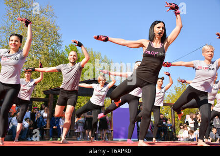 Nis, Serbia - April 20, 2019 Group of people participating in the free public Piloxing class in summer at park on sunny spring day - Stock Image