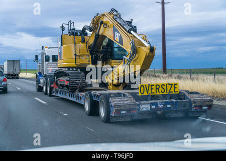 A new Caterpillar excavator on a low boy trailer traveling north on Interstate 5 in California's Central Valley - Stock Image