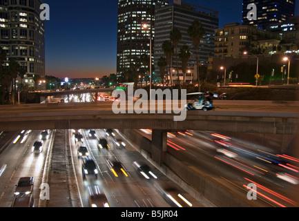 US 101, Harbor Freeway LA skyline, Dusk Los Angeles, California, USA Traffic moving CA Golf Cart pulling woman funny - Stock Image